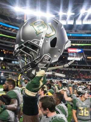 A Baylor Bears player holds up his helmet during a 2015 game.