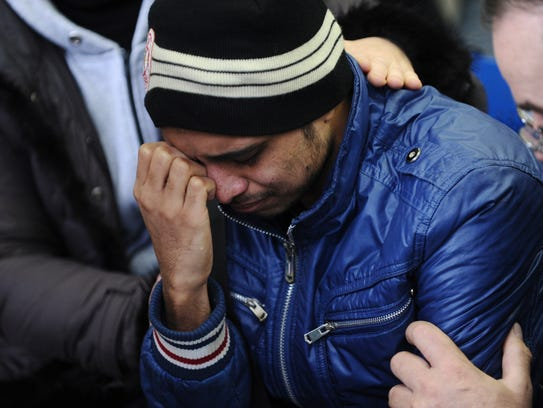 A relative of the plane crash victim sobs as he is