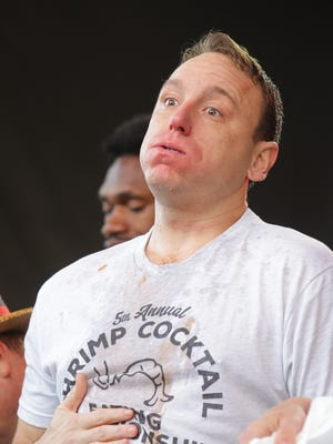 Joey Chestnut holds his stomach after winning the 5th annual Shrimp Cocktail Eating Championship, held at the Meijer Tail Greater event on Georgia St. for the Big Ten Championship in Indianapolis Ind. on Saturday, Dec. 2, 2017.