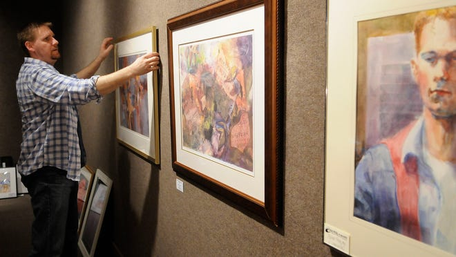 Doug Bancroft, director of exhibits, hangs artwork on the walls Tuesday morning in the Port Huron Museum.