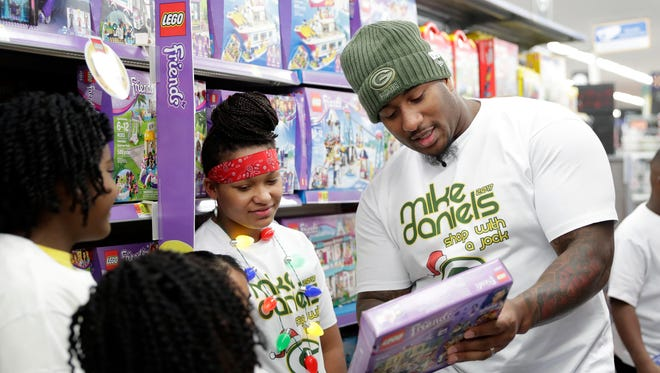 Green Bay Packers defensive tackle Mike Daniels examines Legos with Big Brothers Big Sisters shoppers during the Shop with a Jock event Dec. 11, 2017, at the Walmart on West Mason Street in Green Bay, Wis.
