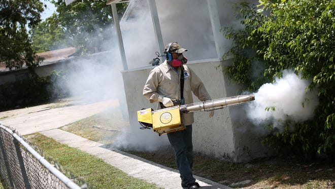 A Miami-Dade County mosquito control inspector sprays pesticide to control the Zika virus outbreak.