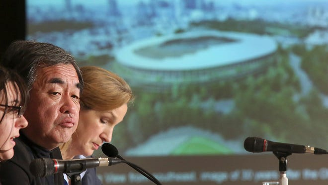 Japanese architect Kengo Kuma, second left, speaks about his design of the 2020 Tokyo Olympic stadium during a press conference in Tokyo on Jan. 15.