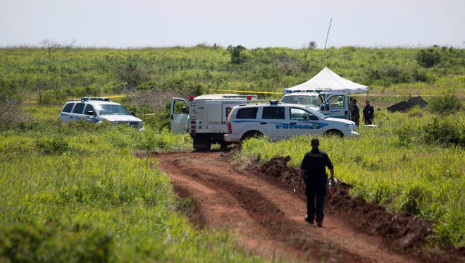 Officials at the site of a plane crash in Lanai City, Hawaii.