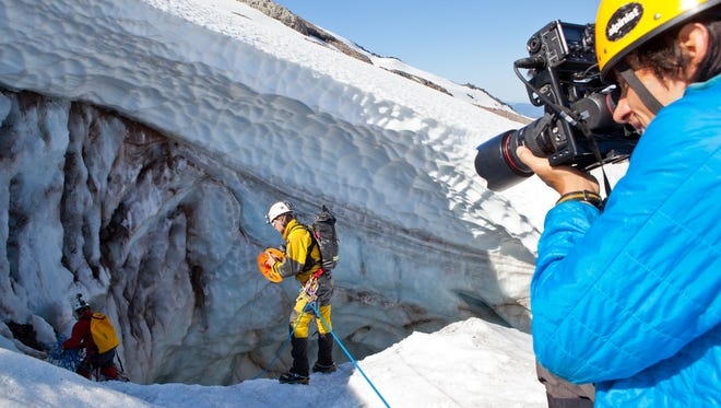 "Photographer Andy Maser, right, photographs caver Eddy Cartaya, center, near a glacier cave in the Mount Hood Wilderness area in Oregon for an episode of ""Oregon Field Guide"" for Oregon Public Broadcasting in 2013."