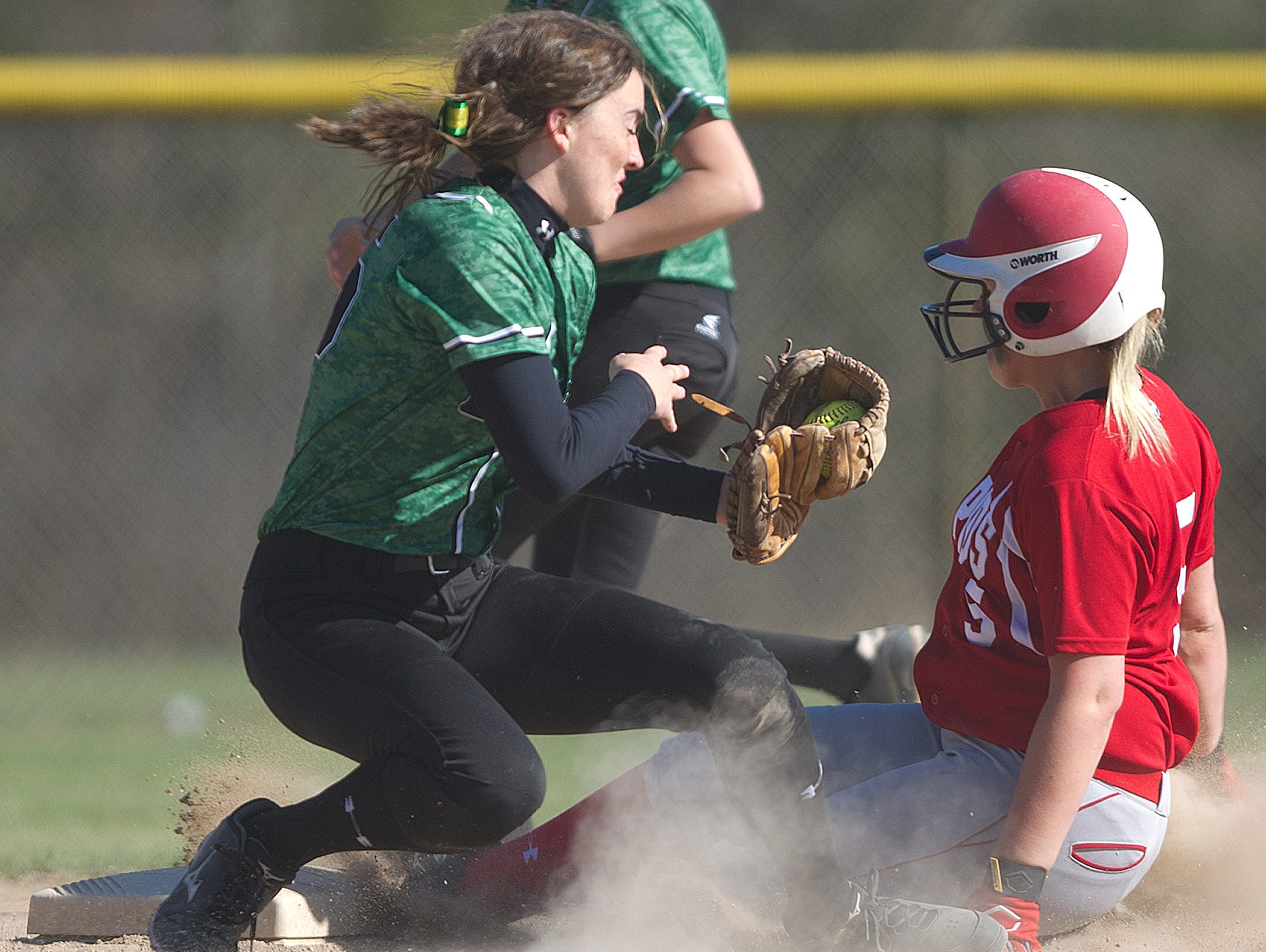D.C. Everest's Ally Dzurka, left, tries to tag out Wisconsin Rapids' Madison Bogie during a Wisconsin Valley Conference softball game Thursday at Lincoln High School in Wisconsin Rapids.