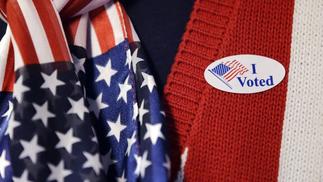 "A voter wears a ""I voted"" sticker."