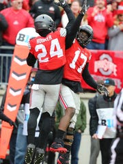 Ohio State's Malik Hooker (24) and Jerome Baker celebrate after Hooker's pick-6 in Saturday's 30-27 double overtime victory over Michigan.