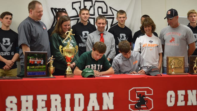 Clay Fisher (bottom left) and Joey Palumbo sign their national letters of intent Wednesday. Looking on are Clay's parents Doug and Nicci Fisher, Coach J.D. Walters (middle), Joey's parents Norm and Michelle Palumbo and the senior members of Sheridan 'Squad 16.'