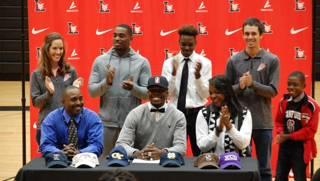 Liberty High School senior Keyshawn King, center, a two-time triple jump state champion, signs to continue his track and field career at Stanford University.