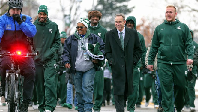Michigan State Spartans head coach Mark Dantonio walks his team over to the stadium prior to a game against the Rutgers Scarlet Knights at Spartan Stadium.