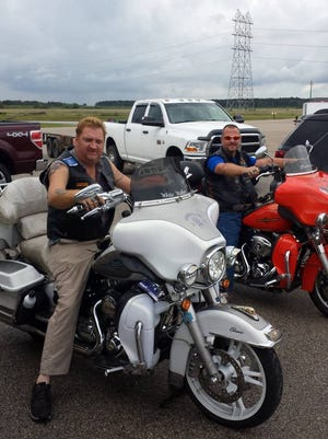 Shelton Foster (left) and Mike Wall, both of Dry Prong, sit on their Harley-Davidson motorcycles at a track where they would later attempt to set a record for the longest motorcycle ride with no hands. The attempt failed when Foster's motorcycle slid on a wet track. Foster said they will try again, possibly in a couple of months.
