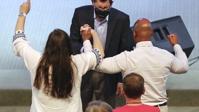 Pastor Jacob King prays over a couple during the altar call as The Church at Liberty Square resumed Sunday services in Cartersville, Ga., on Sunday, June 7, 2020.