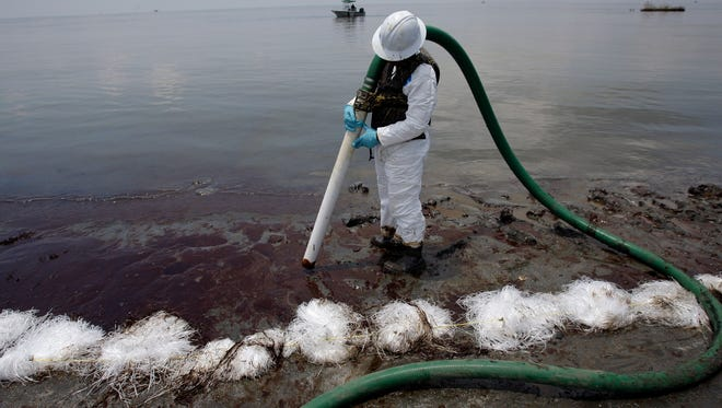 In this June 9, 2010, file photo, a worker uses a suction hose to remove oil washed ashore from the Deepwater Horizon spill in Belle Terre, La.