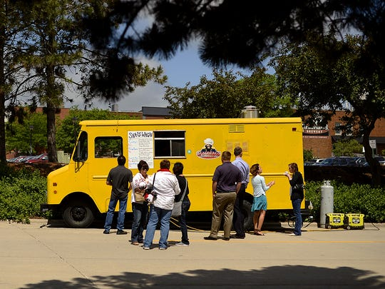 Customers line up near the Skaliwagon, owned by Chef Chris Wiltfang from Skaliwags in Algoma, during the Food Truck Friday event in downtown Green Bay on Friday, June 12, 2015. The event is put on by On Broadway.