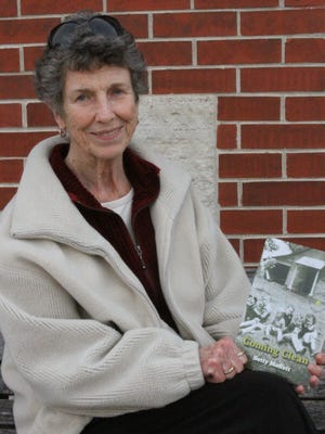 "Grinnell's Betty Moffett holds an early copy of her book titled ""Coming Clean."""