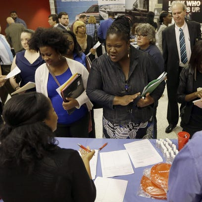 In this photo taken in June, job seekers attend a job