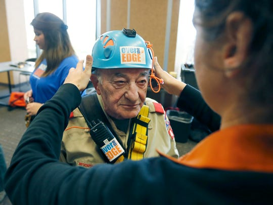89-year-old Joe Aiello of Henrietta gets a helmet fitted before rappelling down the side of the First Federal Plaza Building.
