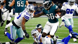 Eagles running back Jay Ajayi (36) fights off a tackle attempt by Dallas Cowboys' Anthony Hitchens (59) in the first half Sunday night.