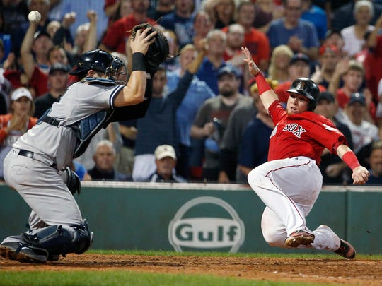 Boston Red Sox's Christian Vazquez, right, scores as