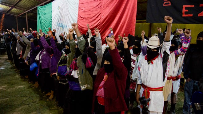 Masked members of the Zapatista National Liberation Army, EZLN, raise their fists during an event marking the 20th anniversary of the Zapatista uprising in the town of Oventic, Chiapas, Mexico.