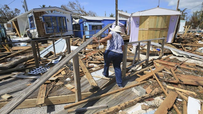 Mirta Mendez walks through the debris at the Seabreeze trailer park along the Overseas Highway in the Florida Keys on Tuesday. Florida is cleaning up and embarking on rebuilding from Hurricane Irma, one of the most destructive hurricanes in its history.
