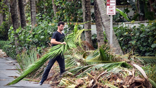 Blake Robinson, with Arbor Tree and Landscape works on cleaning up a property at Queens Lane and North Ocean Boulevard in October 2017. The town is urging residents not to place yard debris outside as Hurricane Isaias approaches Florida.