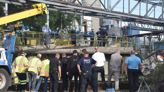 Rescuers prepare to remove a car from the water at the Monroe Power Plant today.