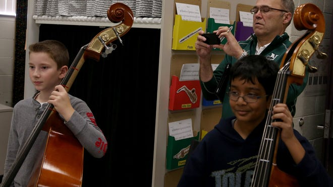 Steve Matthews, the superintendent of Novi Community Schools, takes pictures with his iPhone as Constantin Lucas, 11, left, and Sriker Sureddi, 11, play the bass in Kristen Hurd's orchestra class at Novi Meadows Elementary School in Novi on Oct. 10.
