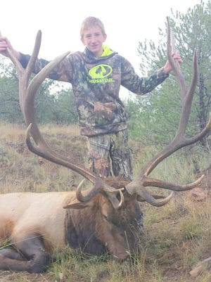 Xavier Koury poses with his 380 bull elk after he harvested it in the Fort Bayard area of Unit 24.