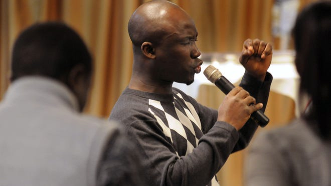 Rev. Moses Ndama, delivering a sermon at Dover's Freedom Christian Fellowship Church, worries about his father in Liberia.