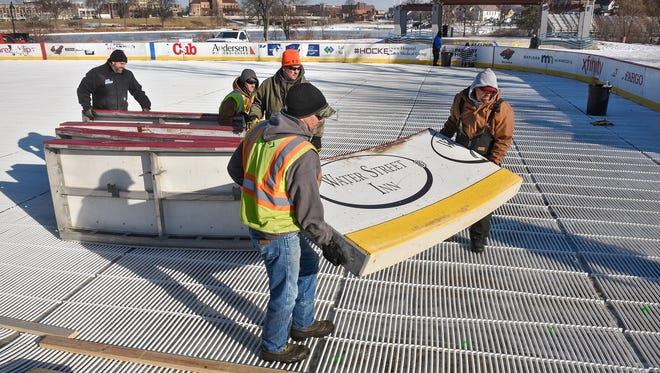 Crew members lift sections of the boards into place at the Hockey Day Minnesota rink Tuesday, Jan. 9, at Eastman Park near Lake George in St. Cloud.