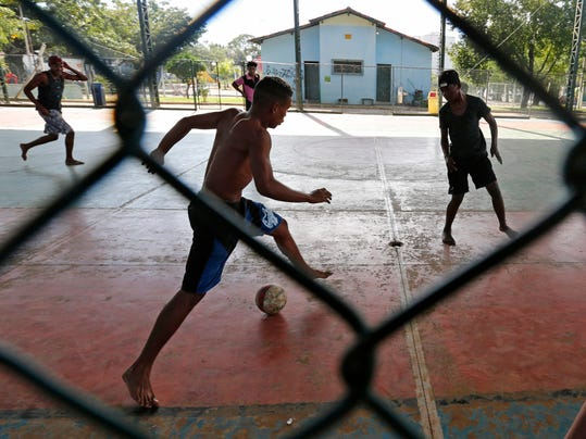 In this Sunday, June 8, 2014 photo, Brazilian boys play street soccer in a collapsing old hangar in Itu, on the outskirts of Sao Paulo, Brazil. Every Sunday, across this nation of rain forests and legendary beaches, groups of kids flock to makeshift pitches like this one to play impromptu tournaments where everyone is welcome. (AP Photo/Shuji Kajiyama)