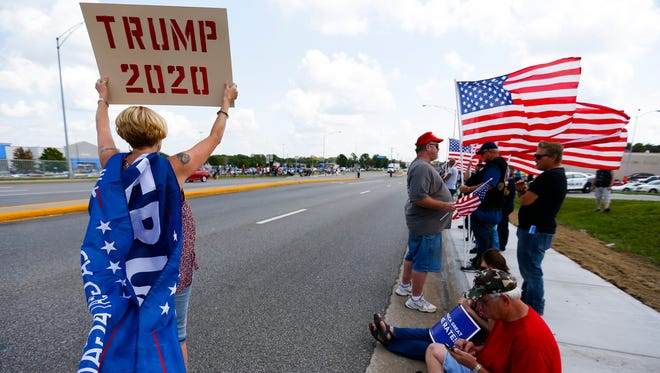 Angela Schudy from Nixa holds a Trump 2020 sign at a rally in support of the president on Kearney Street, just blocks away from where he was speaking on Wednesday, Aug. 30, 2017.