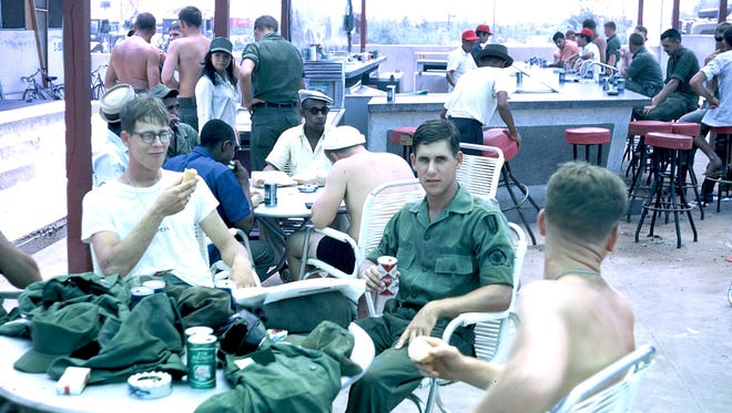 Tim Blessing, holding the Coke can, was on a one-day leave at Vung Tau, when he met Colin Gibson, an Australian soldier, and they swapped uniforms. Blessing kept Gibson's shirt and years later, tracked him down, and the two men have become friends. Gibson is one of the shirtless men in the background.