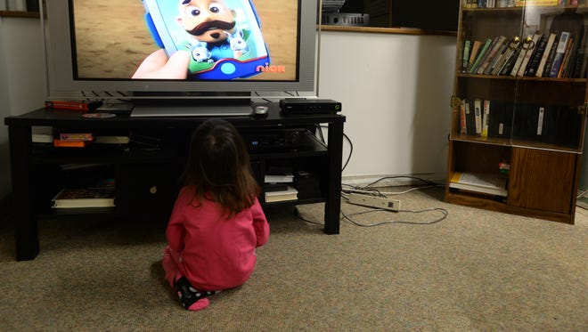 A little girl watches television while staying at the Genesis shelter in Richmond.