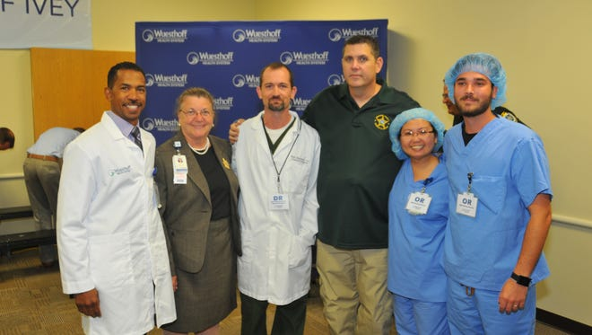 The operating room team at Wuesthoff Medical Center – Rockledge poses for a photo with Deputy Smith.