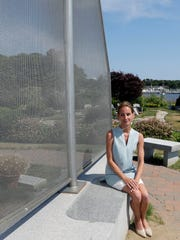 Danielle Hetu poses after speaking about the Westerly Yacht Club's membership policy as the yacht club is seen in background, right in Westerly, R.I.