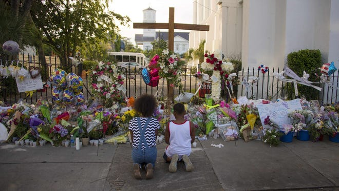 Two children pray near thousands of flowers and cards left in condolence outside Emanuel AME Church  in Charleston.
