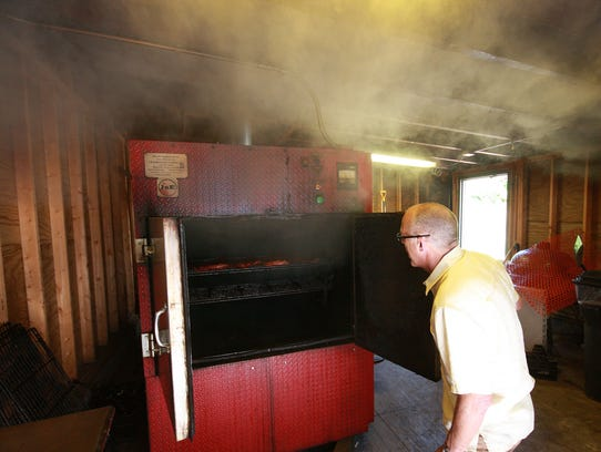 Tim Suprise opens up the meat smoker to check on a