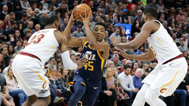 Dec 30, 2017; Salt Lake City, UT, USA; Utah Jazz guard Donovan Mitchell (45) controls the ball between Cleveland Cavaliers forward LeBron James (23) and Cavaliers center Tristan Thompson (13) during the second half at Vivint Smart Home Arena. Utah Jazz won 104-101.  Mandatory Credit: Chris Nicoll-USA TODAY Sports