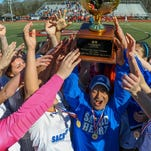 Sacred Heart coach Joe Falla Sr. and his players hoist the trophy following their 1-0 overtime win in the 1A, 2A,3A Girls Soccer Championship held in Clinton Saturday.