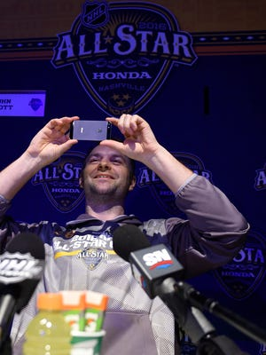 NHL All-Star John Scott snaps a picture of the media after answering questions from the media for NHL All-Star weekend at Bridgestone Arena Friday Jan. 29, 2016, in Nashville, Tenn.