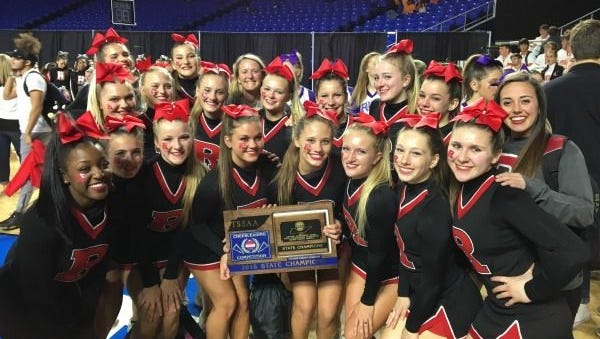 Ravenwood High School's cheer team poses with its state championship plaque in November. The team recently won a national championship.