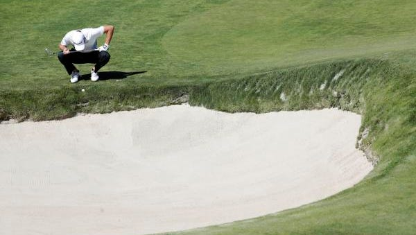 Mickey DeMorat of EFSC checks his lie near a bunker on the second hole during the first round of the U.S. Open Golf Championship.