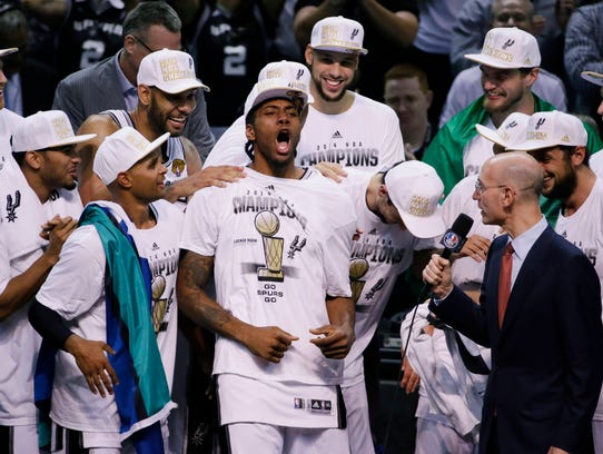 Most Valuable Player San Antonio Spurs forward Kawhi Leonard, center celebrates with the team after Game 5 of the NBA basketball finals against the Miami Heat on Sunday, June 15, 2014, in San Antonio. The Spurs won the NBA championship 104-87. (AP Photo/Tony Gutierrez)
