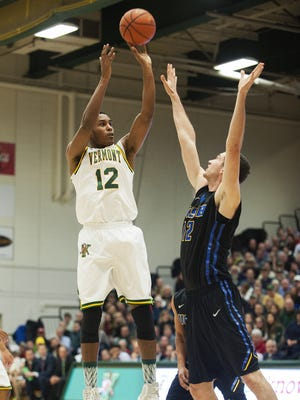 Catamounts forward Darren Payen (12) takes a shot over Santa Barbara forward Alex Hart (12) during the men's basketball game between the UC Santa Barbara Gauchos and the Vermont Catamounts at Patrick Gym on Wednesday night.