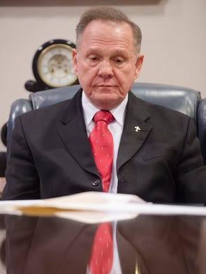 Alabama Chief Justice Roy Moore looks down at his order