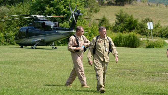 Two individuals walk away from a helicopter that just landed near  the mobile command center at the Deerfield Volunteer Fire Department in Deerfield on Wednesday, August 27, 2014. The helicopter is one of several being used in a search and rescue mission to locate the missing pilot of an F15c fighter jet which crashed into a mountain near Elliotts Knob in Augusta County.