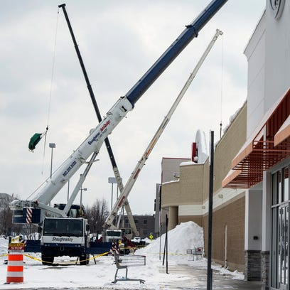 Workers use cranes to clear snow from the roof of a